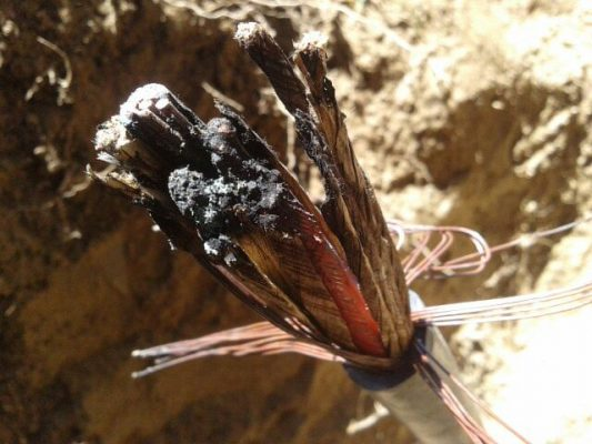 Picture of cut and burnt fiber optic cable in ground.